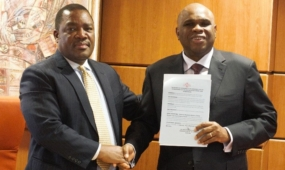 Afreximbank Prof. Benedict Oramah (right) displays the instrument of accession from Eswatini as he shakes hands with Promise Msibi, Permanent Representative of Eswatini to the African Union and Ambassador to Ethiopia, during the ceremony in Cairo.